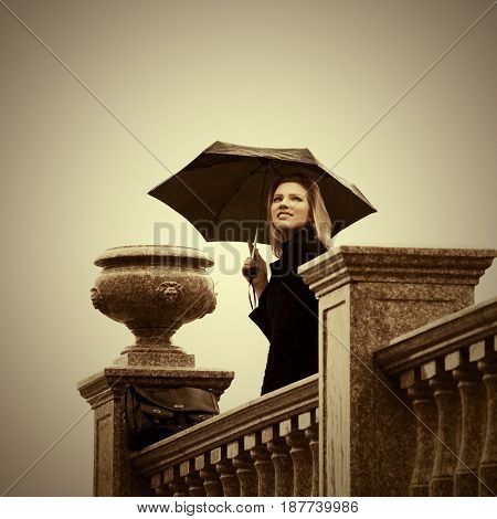 Happy young woman with umbrella walking in city street. Stylish fashion female model outdoor