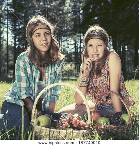 Happy young girls with a fruit basket on nature. Stylish fashion model outdoor