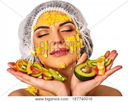 Facial mask from fresh fruits for woman . Girl in medical hat give slices of avocado, grapefruit and kiwi as ingradients for face care smooth skin on isolated. Squeezed fruit on the palm of girl.