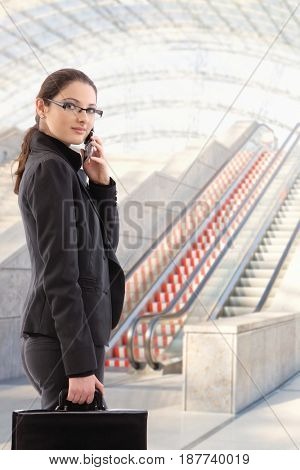Busy young businesswoman going to work, holding suitcase, calling, looking at camera.