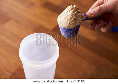 Close Up Of Man Mixing Protein Shake In Cup