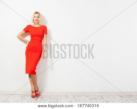 Beautiful happy woman in red dress. Female against a white wall