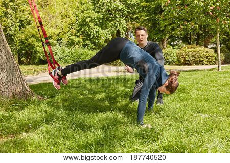 Woman sling training with fitness trainer at the park