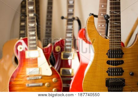 Electric guitars resting on a guitar stand in room or studio.