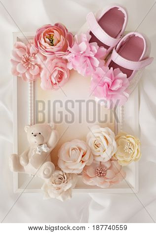 close-up of photo frame, baby shoes and flowers