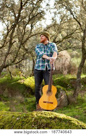 Hipster man with red beard and a guitar relaxs in the field