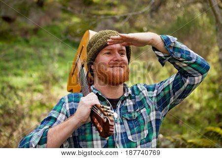 Hipster man with red beard holding a guitar and looking for something in the forest