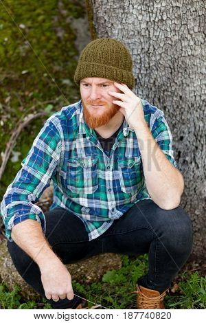 Pensive red haired man in th forest