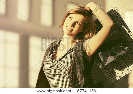 Happy young fashion woman with shopping bags in a city street