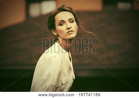 Sad young business woman walking in a city street. Stylish fashion model in white blouse outdoor