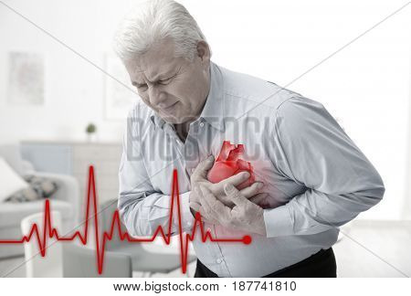 Heart attack concept. Senior man suffering from chest pain indoor