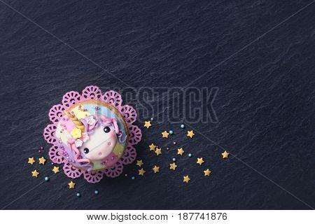 Unicorn cupcakes on a black slate
