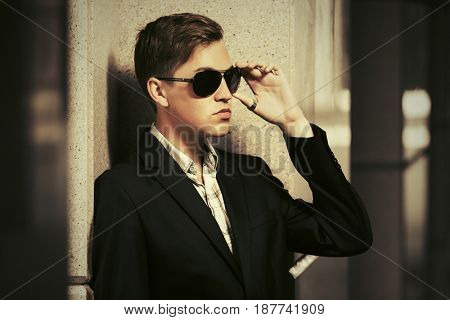 Young handsome man standing at the wall in a city street. Stylish fashion male model outdoor