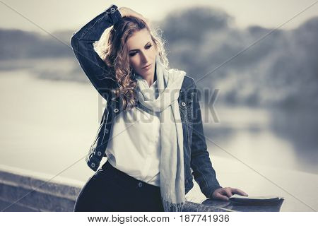 Young business woman with long curly hairs walking by the river. Stylish fashion model in denim jacket outdoor