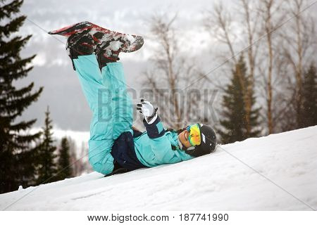 Girl snowboarder resting on the slope by lifting her legs with a snowboard up
