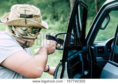 Man with a gun opens the car door.