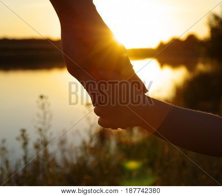 Hands of holding each other on lake and sun