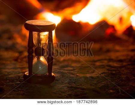 vintage hourglass on fire background in darkness