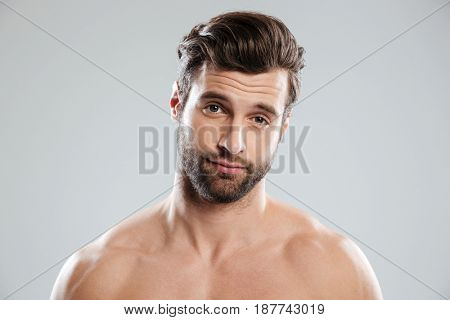 Portrait of a handsome doubtful man with naked shoulders isolated over white background