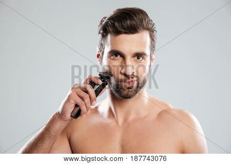 Handsome young man shaving with electric razor isolated over white background