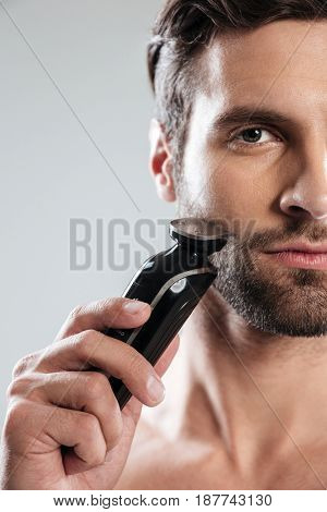 Serious bearded young man shaving with electric razor and looking at camera isolated over white background