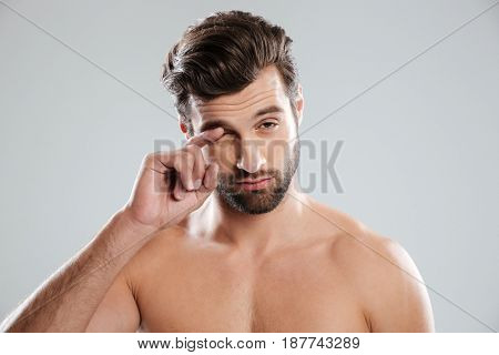 Portrait of a naked sleepy guy scratching his eye isolated over white background