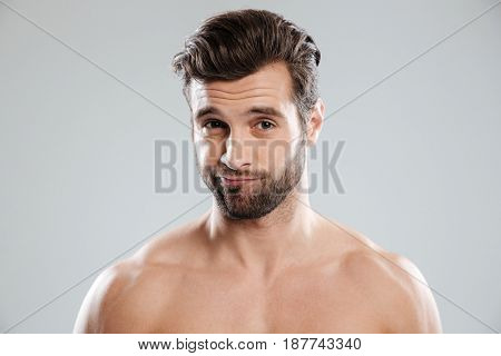 Portrait of a charming doubtful man with naked shoulders isolated over white background