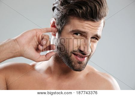 Portrait of a young impolite guy picking his ear and looking at camera isolated over white background
