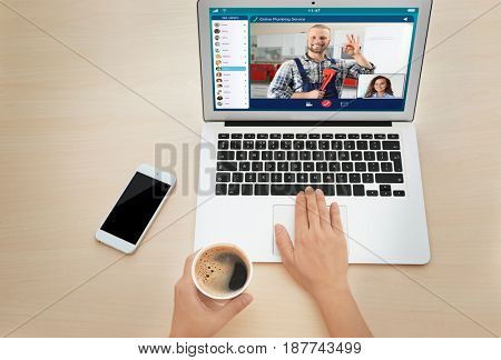 Woman video conferencing with plumber on laptop. Online service concept