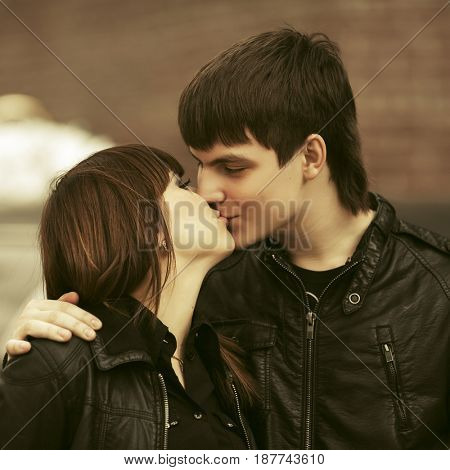 Happy young couple in love kissing in city street. Stylish fashion male and female model in leather jackets outdoor