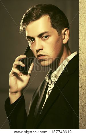 Young handsome business man calling on mobile phone in city street. Stylish male model in black jacket