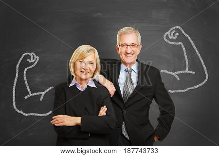 Business team with chalk muscles on blackboard as strength and success concept