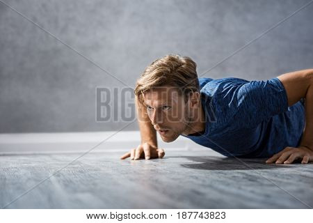 Young athletic man doing push ups on floor. Portrait of muscular and strong guy exercising at gym. Fit handsome athlete doing push ups as part of bodybuilding training.
