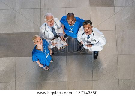 High angle view of doctors and nurses looking at camera during a conference. Cheerful nurses and multiethnic doctors smiling in a modern hospital hallway. Team of medical people in clinic.