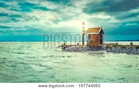 Lighthouse on sea shore with lighting lantern dramatic evening cloud on the sky of sunset panoramic view water landscape.
