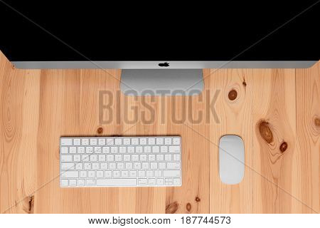 UKRAINE, RIVNE, May 4, 2017. Apple Computer iMac 27 retina display 5K keyboard and magic mouse isolated on a wood background