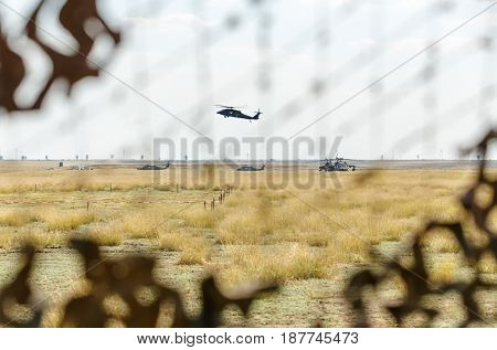 An US Army chopper, seen through camouflage, flies overhead during the NATO 'Wind Spring 15' military exercise at Smardan military shooting range, in Romania, on April 21, 2015.