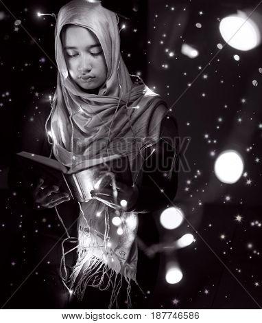 Muslim woman praying in dark room with nice lights around her
