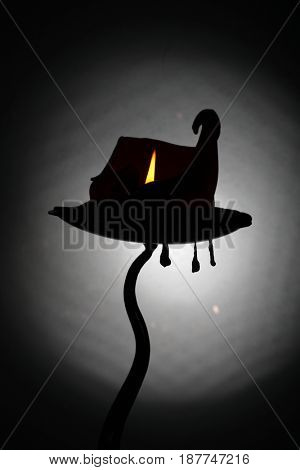 A gnarled curling burning candle that resembles a witches hat / haunted house, with three wax pendant drips suspended from the candle holder.