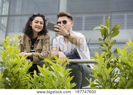 Two young smiling people boyfriend and girlfriend talk and have great fun. Photographed the mobile phone