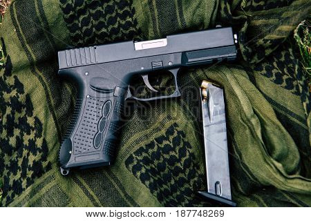 A pistol with a magazine on a green background.