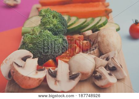 Organic raw vegetables slices on bright geometric background. Healthy food, copy space. Ingredients for salad or soup - mushroom, cherry tomato, broccoli, cucumber, carrot