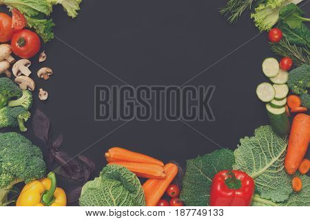 Healthy vegetarian food background. Frame of fresh organic vegetables on black.