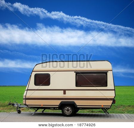 Vintage caravan on a parking lot with blue sky