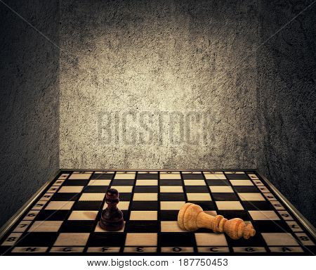 Magical room with a chess board floor surrounded by concrete walls as limitations and the king piece falling down beaten in front of the pawn figure. Business fail and mismanagement concept.
