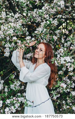 Red-haired Girl With Freckles Near The Apple Tree