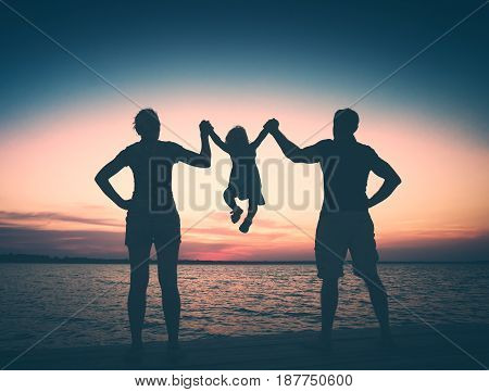 Happy family with baby girl having fun at sunset on a sea. Instagram stylisation.