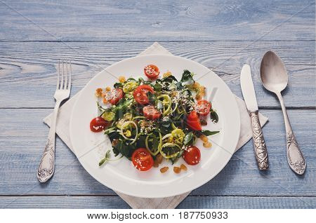 Restaurant dish, served table. Close-up of vegetable salad with tomatoes and greenery on rustic wooden desk, top view