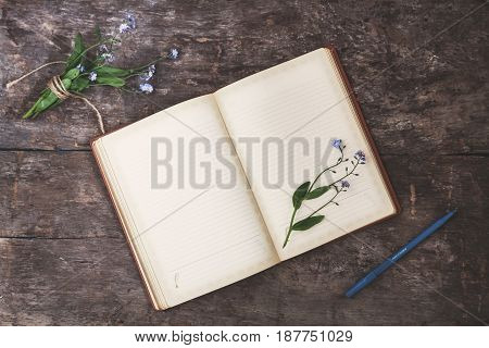 On An Old Wooden Background Lies An Old Notebook And A Bouquet Of Blue Forget-me-nots, A Top View. T