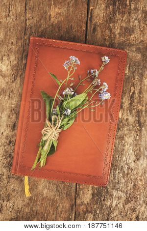 Old Leather Notebook Book, It Is A Bouquet Of Flowers Forget-me-nots. Top View, Close-up View